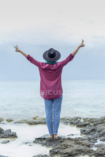 Back view of young woman with dyed blue hair standing on rock in front of the sea showing victory signs, Spain — Stock Photo