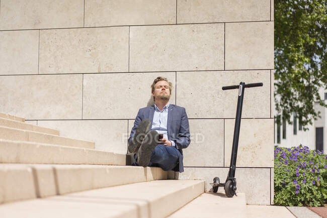 Бізнесмен з E-Scooter і смартфон сидять на кроках відпочинку — стокове фото