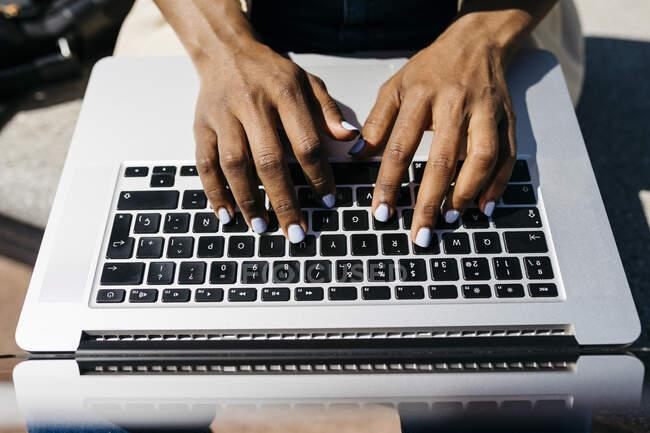 Mujer de negocios sentada en el banco y utilizando el dedo portátil mecanografía - foto de stock