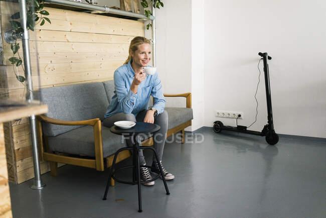 Giovane donna seduta sul divano in un negozio di caffè, e-scooter ricarica in background — Foto stock