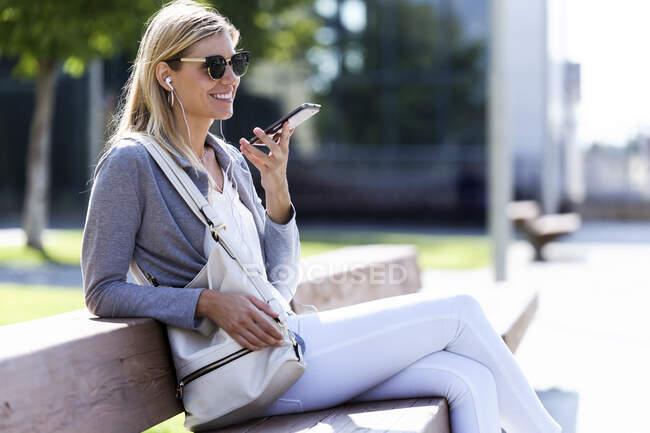 Молода бізнес-леді, яка розмовляє на смартфоні безкоштовно, сидячи на банку. — стокове фото
