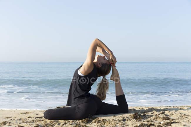 Молодая женщина практикует йогу на пляже, позирует голубям — стоковое фото