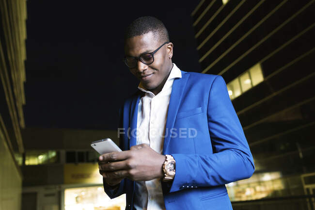 Young businessman wearing blue suit jacket and using smartphone at night — Stock Photo