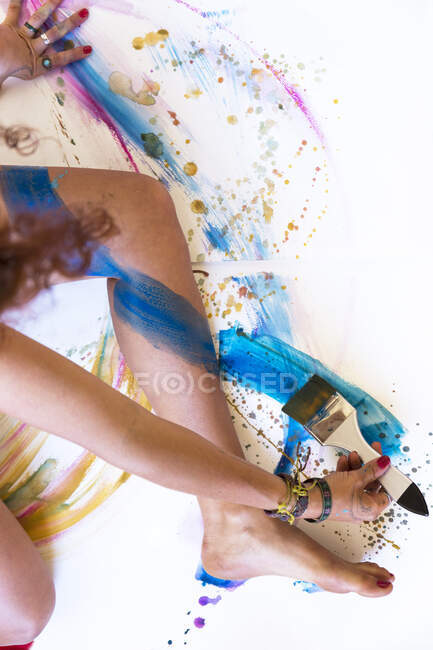 Close-up of woman painting her leg — Stock Photo