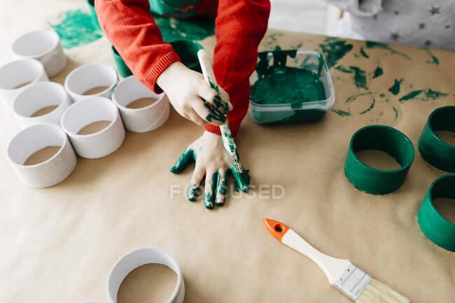 Kind bemalt seine Hände mit Pinsel grün — Stockfoto