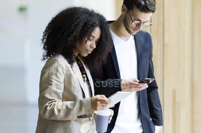 Молодий бізнесмен і бізнесменка користуються планшетом і смартфоном. — стокове фото