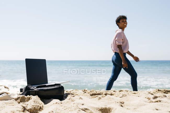 Жінка йде на пляжі, лептоп на мішку. — стокове фото