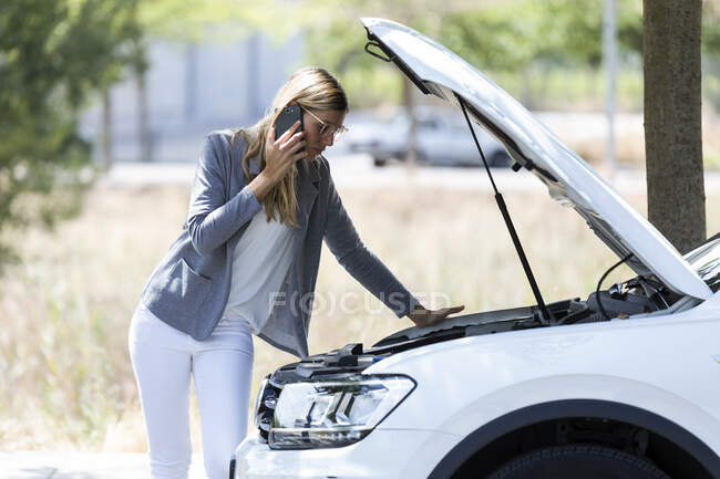 Stressed young woman calling for assistance after breaking down car - foto de stock