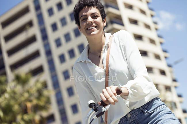 Жінка з велосипедом у місті. — стокове фото