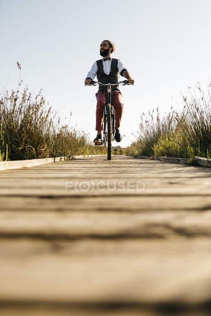 Хорошо одетый человек с велосипедом на деревянной дорожке в сельской местности после работы — стоковое фото