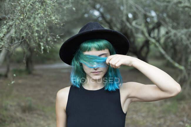Retrato de mujer joven con el pelo teñido azul y verde con sombrero negro en el día lluvioso - foto de stock