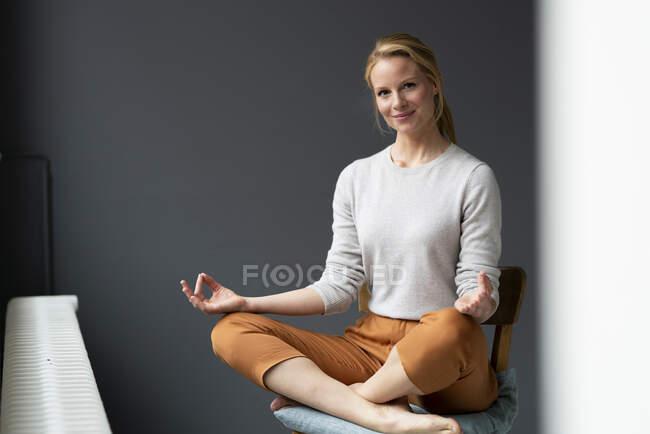 Jovem mulher sentada na cadeira no escritório praticando ioga — Fotografia de Stock