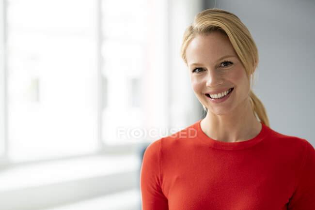 Портрет усміхненої молодої жінки в офісі — стокове фото
