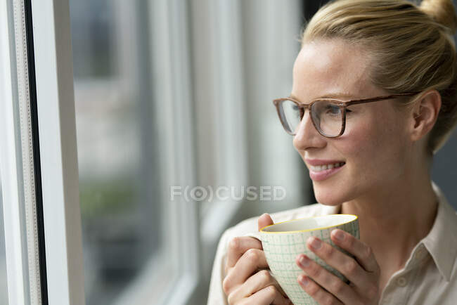 Young businesswoman with cup of coffee looking out of window — Stock Photo