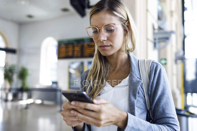 Young woman texting with her mobile phone in the train station hall — Foto stock