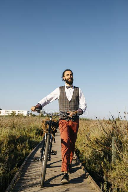 Hombre bien vestido caminando con su bicicleta en una pasarela de madera en el campo después del trabajo - foto de stock