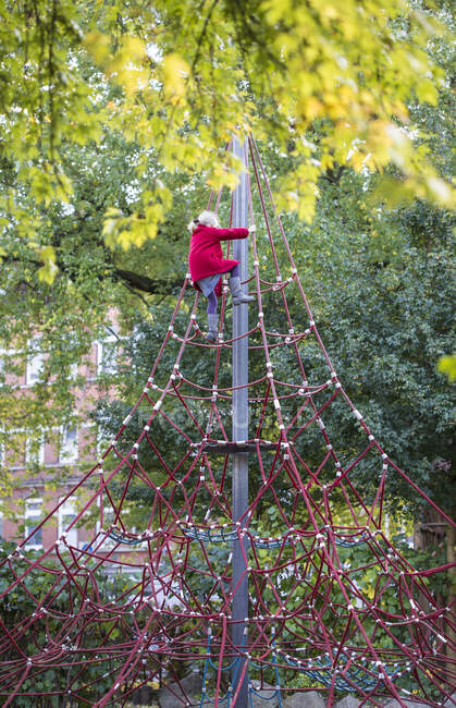 Little girl climbing on jungle gym in autumn — Stock Photo