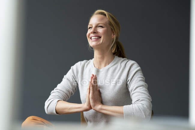 Happy young woman with clasped hands — Stock Photo