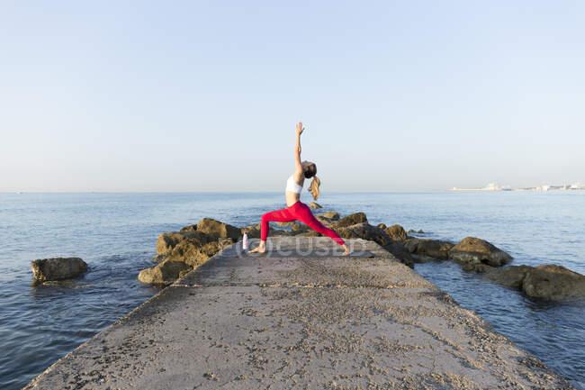 Молодая женщина практикует йогу на пляже, делает позу воина — стоковое фото