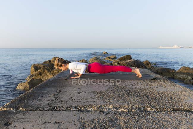 Молодая женщина, практикующая йогу на пляже, занимающаяся чатурангой дандасана — стоковое фото