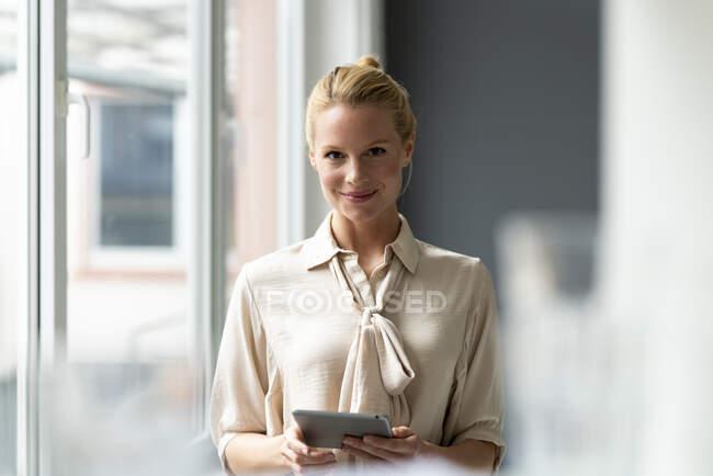 Портрет усміхненого молодого бізнесмена з планшетом на вікні. — стокове фото