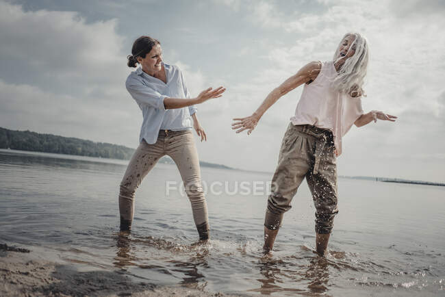 Madre e hija nhaving diversión en la playa, salpicaduras de agua - foto de stock