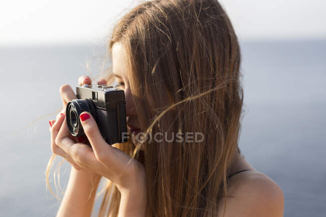 Close up of a female teenager taking a photo outdoors — Stock Photo