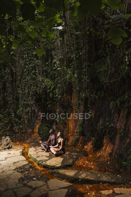 Пара медитирующих у водопада — стоковое фото