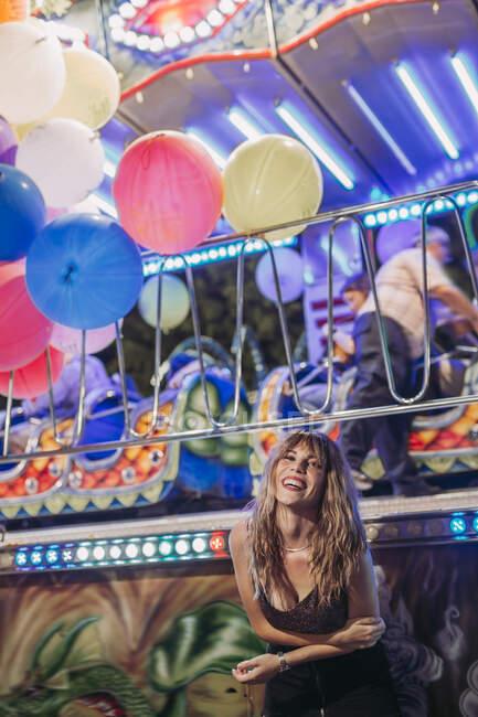 Feliz joven en una feria de diversiones por la noche - foto de stock