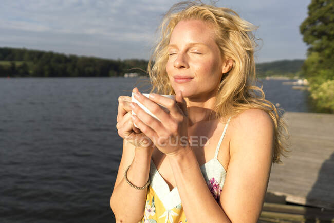 Young woman dwith closed eyes holding a cup at a lake — Stock Photo