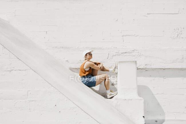 Mujer joven sentada frente a una pared blanca al aire libre - foto de stock