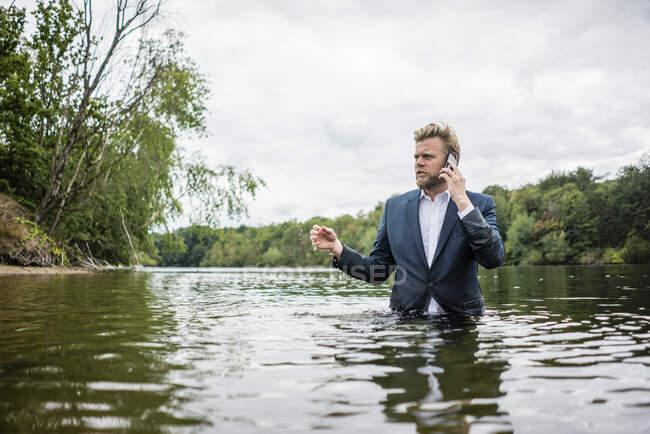 Empresario parado en un lago hablando por teléfono - foto de stock