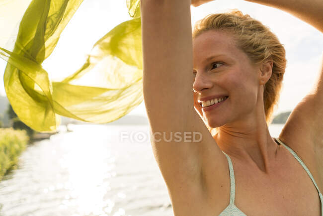 Smiling young woman holding a cloth at a lake — Stock Photo