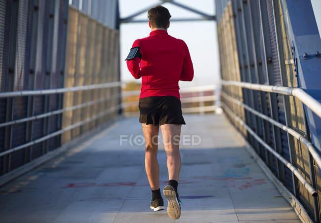 Вид сзади на бегуна со смартфоном в кармане, бегущего по мосту — стоковое фото