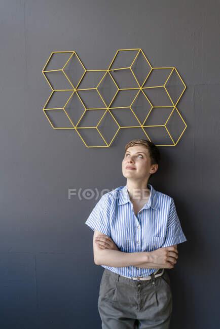 Mulher de pé sob uma estrutura em uma parede — Fotografia de Stock