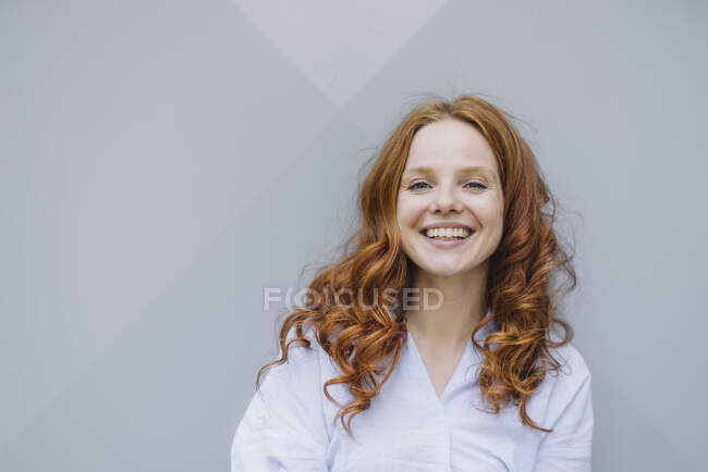 Portrait of happy redheaded woman at a wall — Stock Photo
