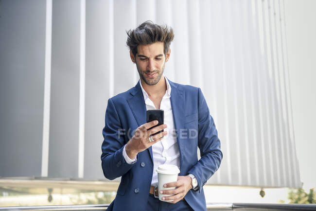 Smiling businessman using smartphone taking a coffee break outdoors — Stock Photo