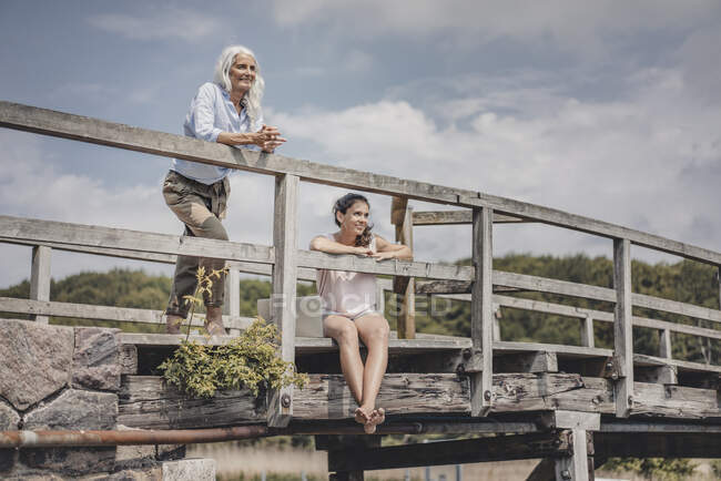 Madre e hija mirando a la vista desde un puente - foto de stock