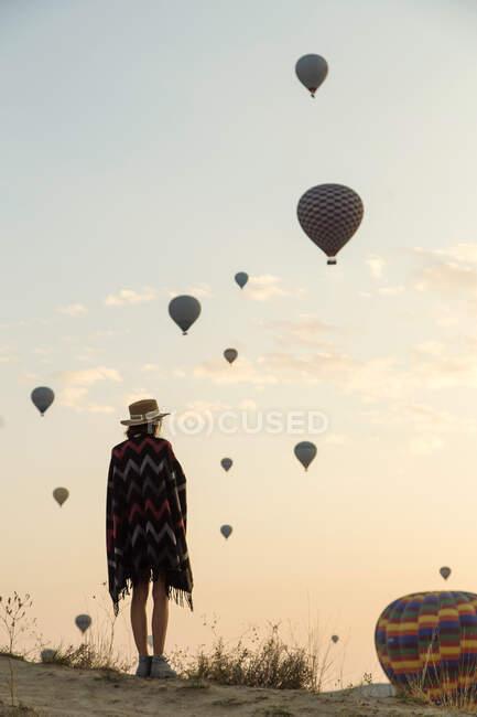 Молода жінка і повітряні кулі ввечері, Горем, Каппадокія, Туреччина. — стокове фото