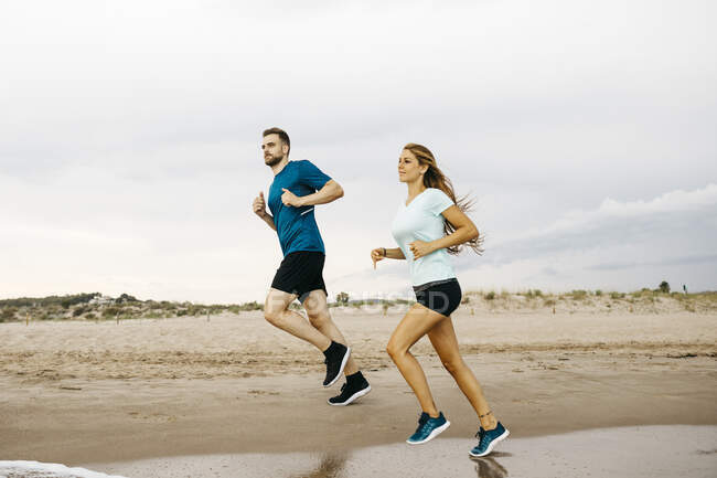 Young couple jogging on the beach — Stock Photo