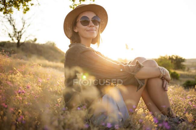 Jeune femme portant un chapeau de soleil et assise sur la prairie au coucher du soleil — Photo de stock