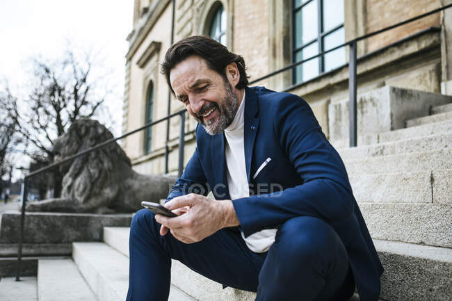 Portrait of smiling mature businessman sitting on stairs looking at cell phone — Stock Photo