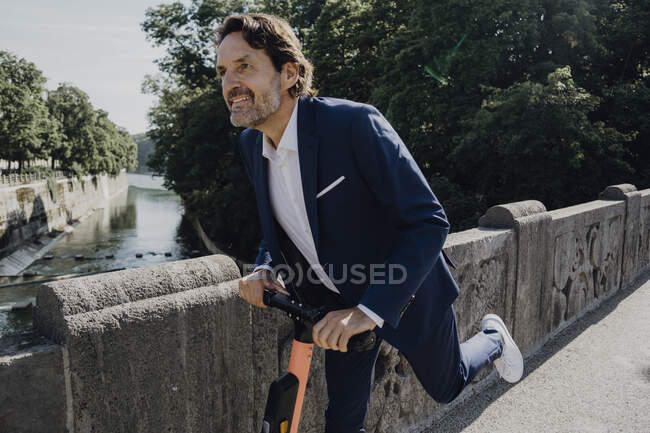 Businessman with e-scooter on a bridge — Stock Photo