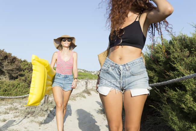 Young women walking to the beach — Stock Photo