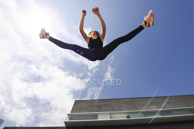 Молодая женщина выпрыгнула на улицу при солнечном свете — стоковое фото