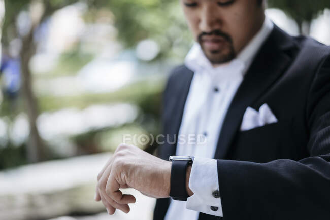 Young businessman in the city checking his smartwatch — Stock Photo