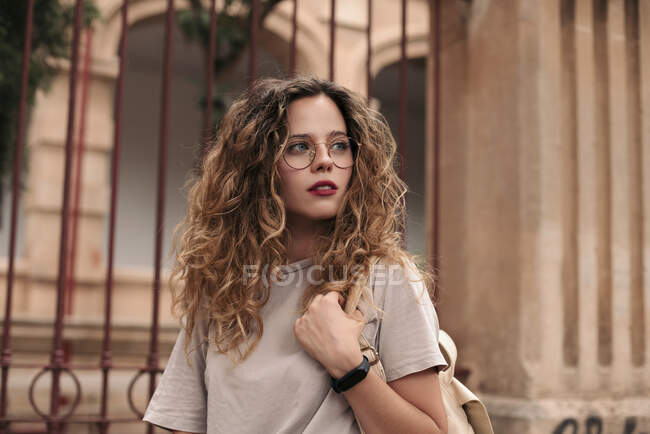 Beautiful young woman with curly hair and glasses in the city — Stock Photo