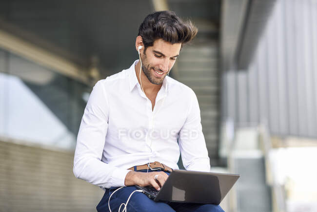 Smiling businessman wearing earphones using laptop outdoors in the city — Stock Photo