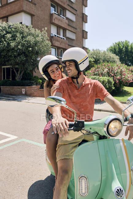 Pareja joven en un scooter vintage - foto de stock