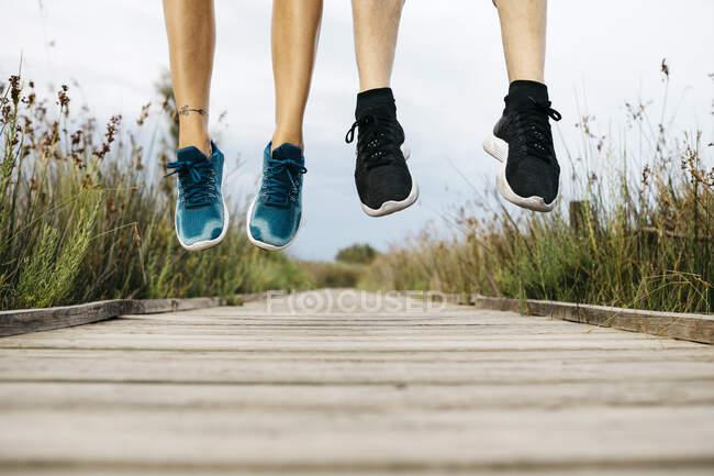 Pies de corredores saltando en una pasarela de madera - foto de stock